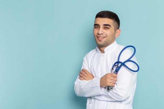 Vorderansicht des jungen männlichen arztes im weißen anzug mit dem blauen stethoskop, das aufwirft und lächelt