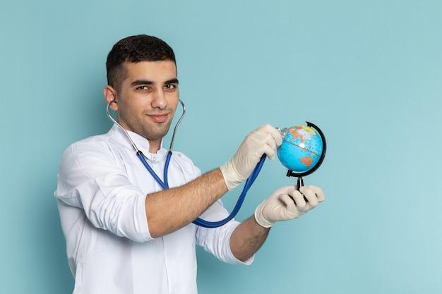 Vorderansicht des jungen männlichen arztes im weißen anzug mit dem blauen stethoskop, das globus lächelt und prüft