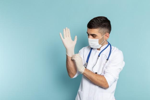 Vorderansicht des jungen männlichen arztes im weißen anzug mit dem blauen stethoskop lächelnd, das handschuhe trägt