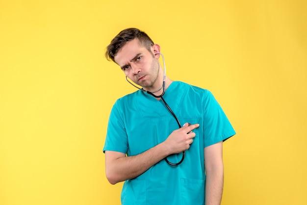 Vorderansicht des jungen männlichen arztes mit stethoskop auf gelber wand