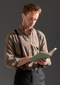 Vorderansicht des jungen männlichen modells lesend