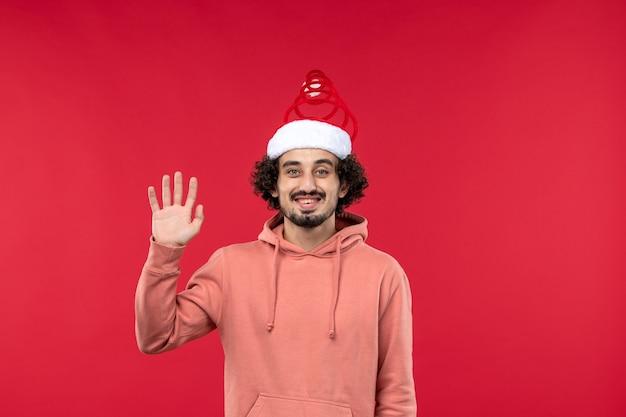 Vorderansicht des jungen mannes, der an der roten wand grüßt und lächelt