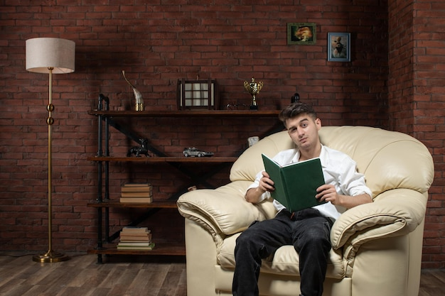 Vorderansicht des jungen mannes, der auf sofa mit heft innerhalb der geschäftsmöbel-büroarbeit des raumes sitzt