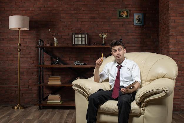 Vorderansicht des jungen mannes, der auf sofa sitzt, das notizen innerhalb der raumarbeitsarbeitsschülerarbeit schreibt