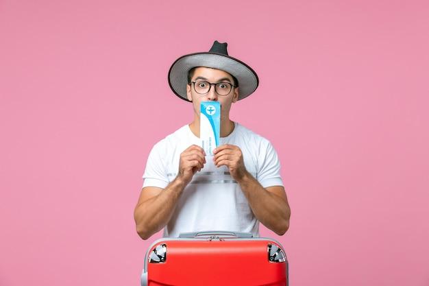 Vorderansicht des jungen mannes, der ein ticket an einer rosa wand hält?