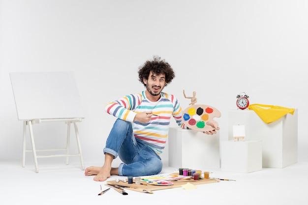 Vorderansicht des jungen mannes, der farben und quaste zum zeichnen auf weißer wand hält