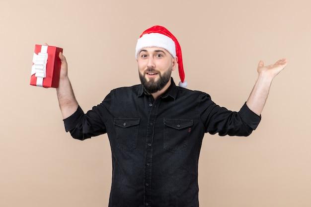 Vorderansicht des jungen mannes, der geschenk an der rosa wand hält