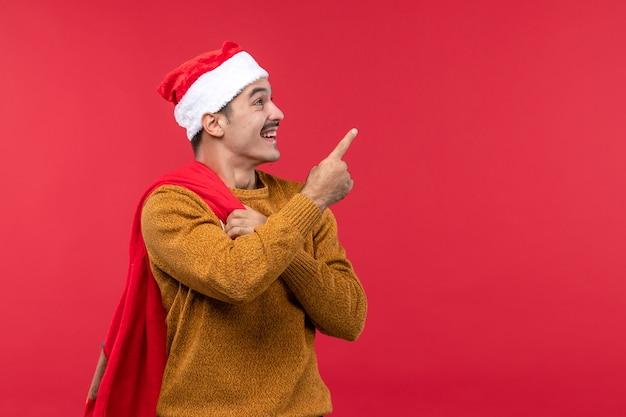 Vorderansicht des jungen mannes, der geschenkbeutel auf hellroter wand trägt