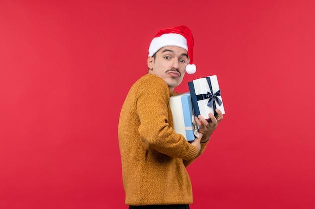 Vorderansicht des jungen mannes, der geschenke an der roten wand hält