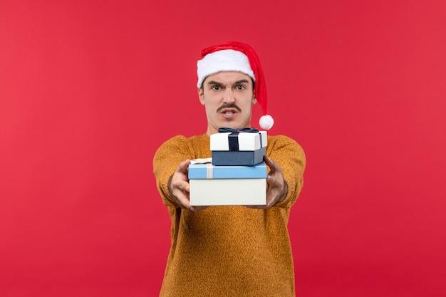 Vorderansicht des jungen mannes, der geschenke auf roter wand präsentiert