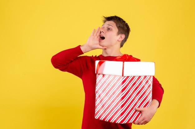 Vorderansicht des jungen mannes, der großes weihnachtsgeschenk hält, das gelbe wand anruft Kostenlose Fotos