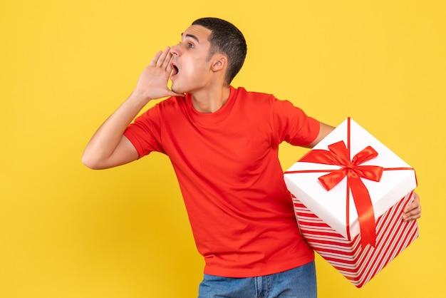 Vorderansicht des jungen mannes, der großes weihnachtsgeschenk hält, das jemanden auf gelber wand anruft Kostenlose Fotos