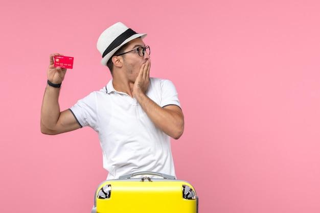 Vorderansicht des jungen mannes, der im urlaub an der rosa wand emotional eine rote bankkarte hält