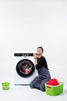 Vorderansicht des jungen mannes, der kleidung mit hilfe der waschmaschine an der weißen wand wäscht