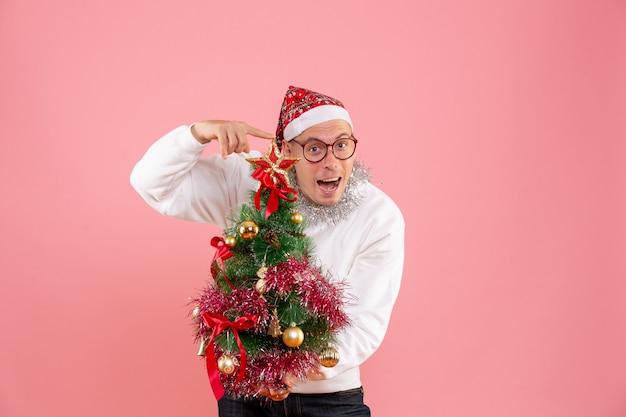 Vorderansicht des jungen mannes, der kleinen weihnachtsbaum auf rosa wand hält
