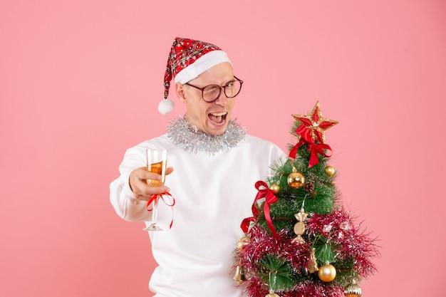 Vorderansicht des jungen mannes, der kleinen weihnachtsbaum hält und auf rosa wand trinkt