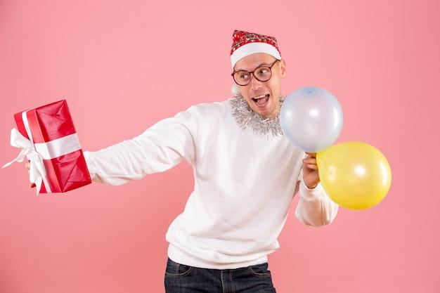 Vorderansicht des jungen mannes, der luftballons hält und auf rosa wand präsentiert
