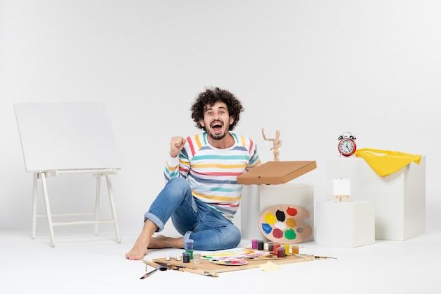 Vorderansicht des jungen mannes, der pizzakarton auf weißer wand hält