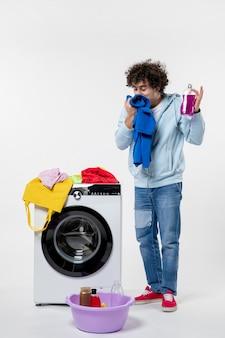 Vorderansicht des jungen mannes, der saubere kleidung aus der waschmaschine an der weißen wand herausnimmt