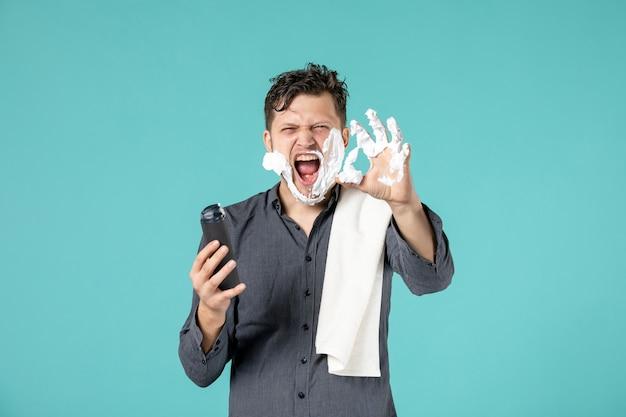 Vorderansicht des jungen mannes, der schaum zum rasieren in sein gesicht an der blauen wand aufträgt