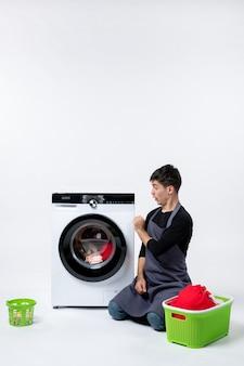 Vorderansicht des jungen mannes, der schmutzige kleidung für die waschmaschine an der weißen wand vorbereitet
