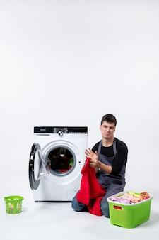 Vorderansicht des jungen mannes, der schmutzige kleidung zum waschen an der weißen wand vorbereitet