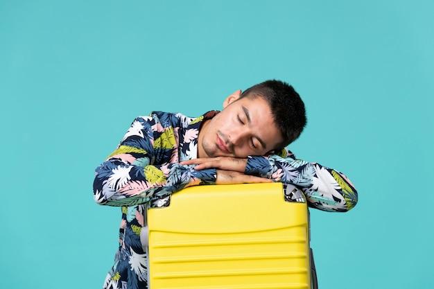 Vorderansicht des jungen mannes, der sich auf urlaub mit gelber tasche vorbereitet, die müde fühlt und auf blauer wand schläft
