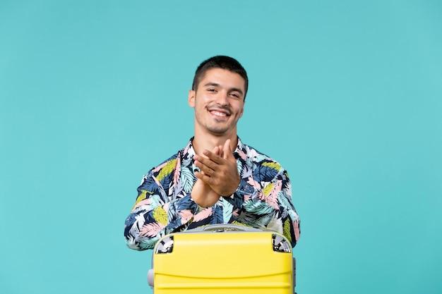 Vorderansicht des jungen mannes, der sich auf urlaub mit klatschendem und lächelndem sack auf blaue wand vorbereitet