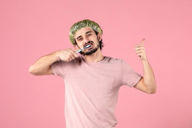 Vorderansicht des jungen mannes, der sich die zähne an der rosa wand putzt