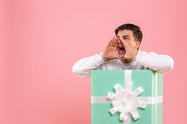 Vorderansicht des jungen mannes, der sich in der gegenwart versteckt und die rosa wand anruft Kostenlose Fotos