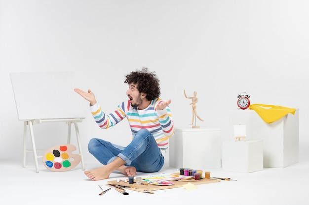 Vorderansicht des jungen mannes, der um farben und zeichnungen auf weißer wand sitzt