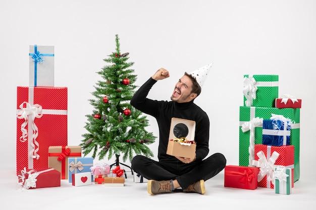 Vorderansicht des jungen mannes, der um feiertagsgeschenke sitzt, hält baumspielzeug auf weißer wand hält