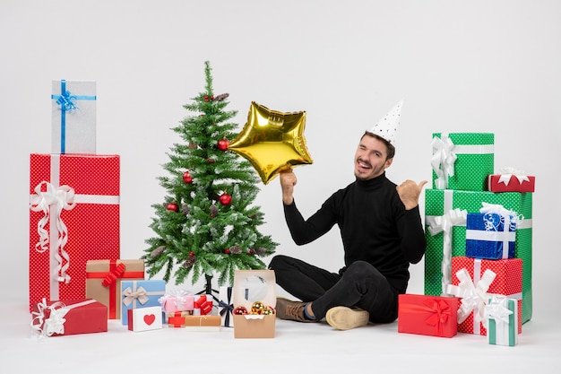 Vorderansicht des jungen mannes, der um geschenke sitzt und goldsternfigur auf weißer wand hält