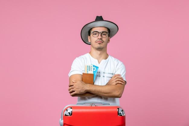 Vorderansicht des jungen mannes, der urlaubstickets in der brieftasche auf dem rosafarbenen boden hält