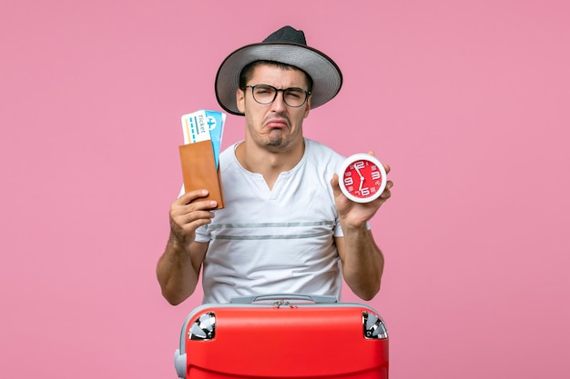 Vorderansicht des jungen mannes, der urlaubstickets und uhr auf rosafarbenem bodenflugzeug hält reisemann reise urlaubszeit sommer trip