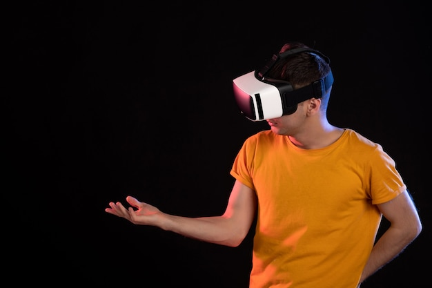 Vorderansicht des jungen mannes, der virtuelle realität an der dunklen wand spielt