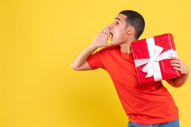Vorderansicht des jungen mannes, der weihnachten an gelber wand hält