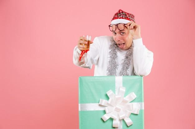 Vorderansicht des jungen mannes, der weihnachten mit getränk auf der rosa wand feiert