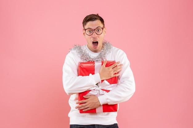 Vorderansicht des jungen mannes, der weihnachtsgeschenk auf rosa wand hält