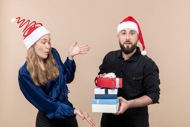 Vorderansicht des jungen mannes, der weihnachtsgeschenke mit frau an der rosa wand hält