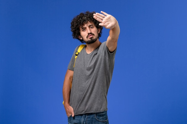 Vorderansicht des jungen mannes im grauen t-shirt, das gelben rucksack an der blauen wand trägt