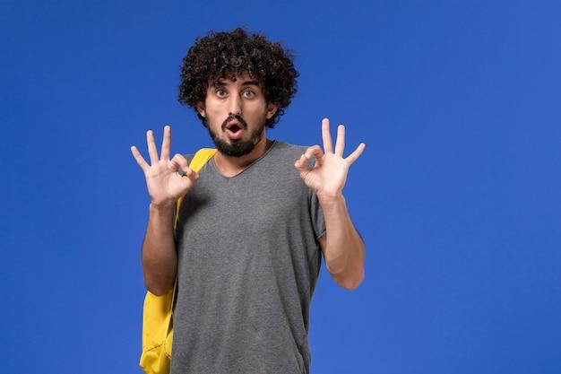Vorderansicht des jungen mannes im grauen t-shirt, das gelben rucksack auf der hellblauen wand trägt