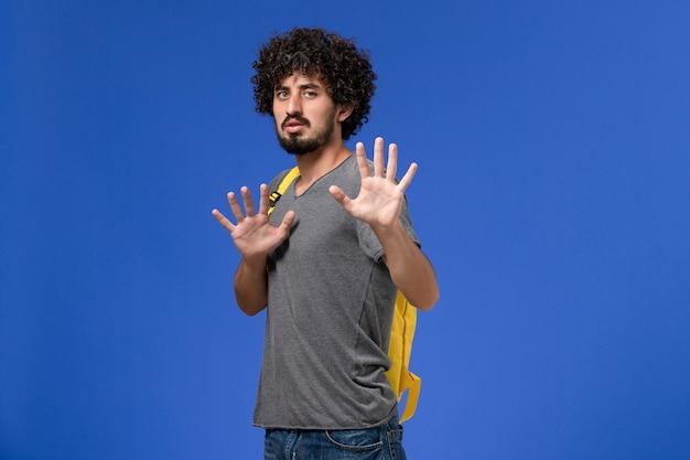 Vorderansicht des jungen mannes im grauen t-shirt, das gelben rucksack trägt, der auf blauem des studentenunterrichts-college-posenmodell lächelt