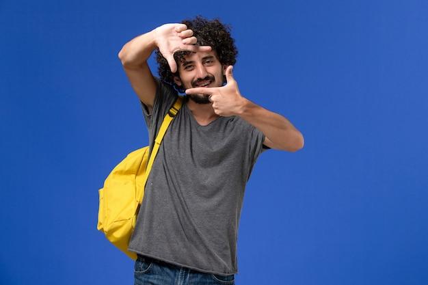Vorderansicht des jungen mannes im grauen t-shirt, das gelben rucksack trägt, der auf blauer wand aufwirft
