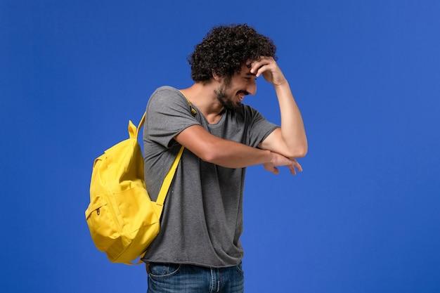 Vorderansicht des jungen mannes im grauen t-shirt, das gelben rucksack trägt, der gerade auf der blauen wand aufwirft und lacht