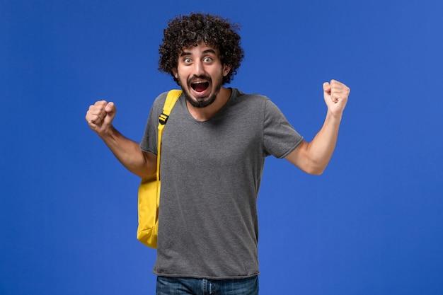 Vorderansicht des jungen mannes im grauen t-shirt, das gelben rucksack trägt, der gerade auf der blauen wand sich freut