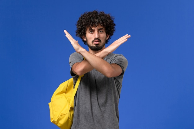 Vorderansicht des jungen mannes im grauen t-shirt, das gelben rucksack trägt, der gerade auf der hellblauen wand aufwirft