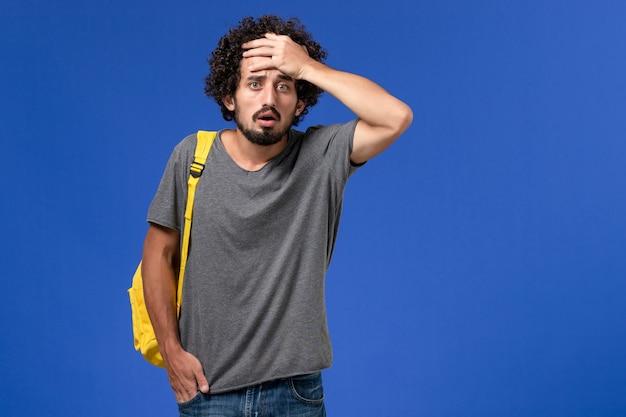 Vorderansicht des jungen mannes im grauen t-shirt, das gelben rucksack trägt, der mit verwirrtem ausdruck auf blauer wand aufwirft