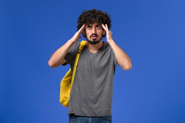 Vorderansicht des jungen mannes im grauen t-shirt, der gelben rucksack trägt, der seine schläfen an der blauen wand hält