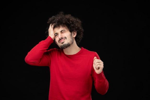 Vorderansicht des jungen mannes im roten hemd auf schwarzer wand